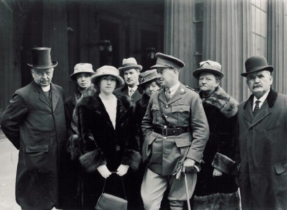 Photo noir et blanc de quatre femmes et de quatre hommes vêtus de manteaux chauds et coiffés de chapeaux devant le palais de Buckingham. L'homme au centre porte un uniforme militaire et s'appuie sur une canne.