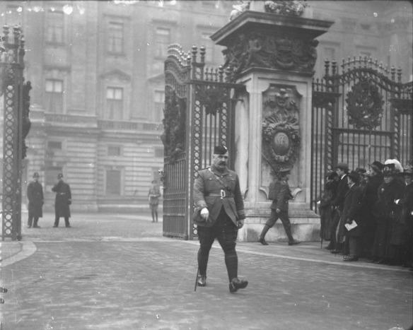 Photo noir et blanc d'un homme moustachu vêtu d'un pantalon écossais, d'une ceinture Sam Browne et d'une casquette, passant des grilles ornementales avec un bâton de marche. À sa droite, une foule regarde vers les grilles.