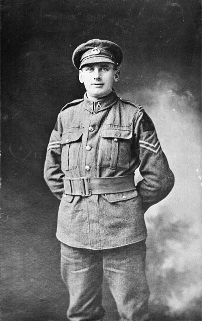 Photo noir et blanc prise dans un studio et montrant un soldat en uniforme, debout, les mains derrière le dos.