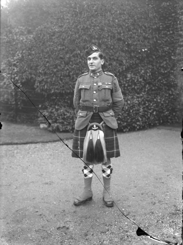 Photo noir et blanc d'un soldat debout vêtu d'un kilt.