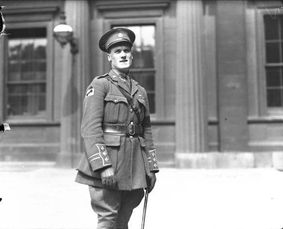 Photo noir et blanc d'un soldat vêtu de sa tenue de service, légèrement de profil, plissant les yeux en raison du soleil.