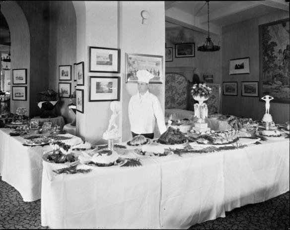 Photo noir et blanc de trois tables dressées pour un buffet officiel, avec un chef cuisinier portant une veste et une toque blanches.