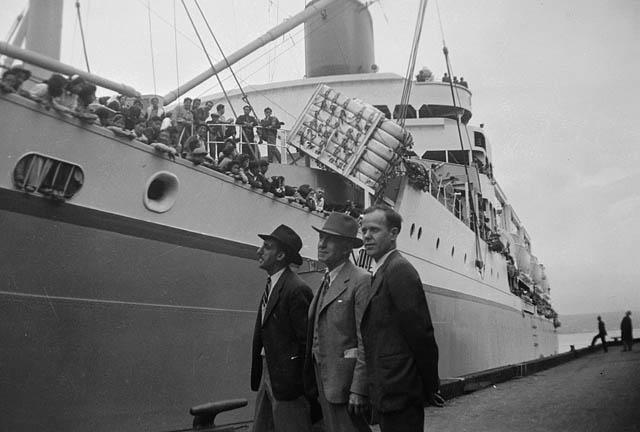 Photo noir et blanc de trois hommes debout devant un bateau.