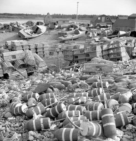 Photo noir et blanc d'un village côtier. On voit des homardiers à l'arrière-plan, des casiers à homard au centre, et des balises flottantes au premier plan.