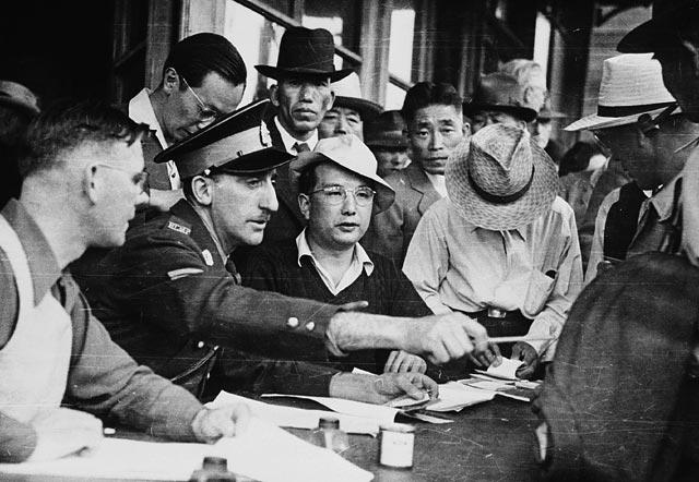 Photo noir et blanc d'un agent de la Gendarmerie royale du Canada assis à une table et examinant des documents, entouré de plusieurs hommes.