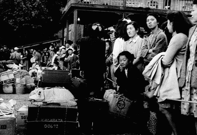 Photo noir et blanc d'un groupe de femmes et d'un enfant, se tenant debout devant des bagages et des caisses.