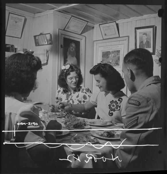 Photo noir et blanc de trois femmes et d'un homme partageant un souper dans la salle à manger d'une maison.