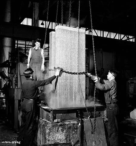 Une photographie noir et blanc d'une femme et de deux hommes manipulant et retirant des blocs d'aluminium de leurs moules à l'aide de chaînes.