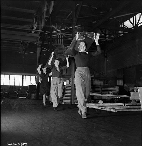 Une photographie noir et blanc de trois femmes transportant ensemble au-dessus de leur tête une longue feuille d'aluminium vers la table d'inspection.