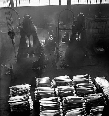 Une photographie noir et blanc montrant une vue en plongée d'une forge d'aluminium produisant des hélices de bombardiers. Il y a plusieurs grandes palettes chargées d'hélices au premier plan.