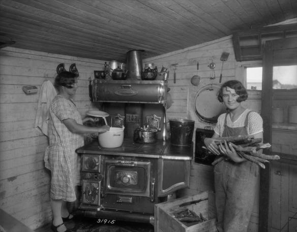 Photo noir et blanc de deux femmes préparant le souper dans une cuisine. À gauche, l'une remue un plat qui cuit dans un chaudron posé sur un poêle à bois. À droite, l'autre tient une brassée de bois.