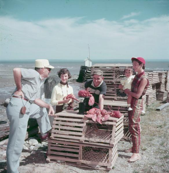Photo noir et blanc de deux hommes, deux femmes et un enfant en train d'examiner quelques homards autour de casiers.