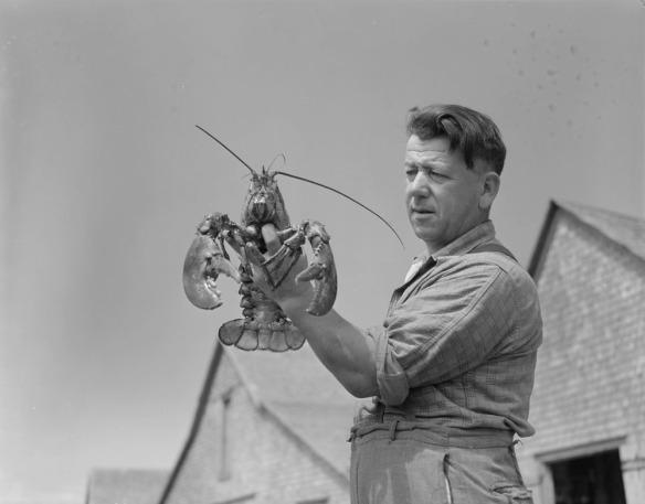 Photo noir et blanc d'un homme tenant un gros homard dans sa main gauche.