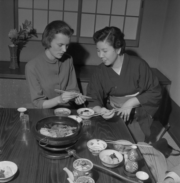 Photo noir et blanc de deux femmes dans un restaurant japonais, assises à une table couverte d'une variété de mets. La femme de droite explique à celle de gauche comment se servir de ses baguettes.