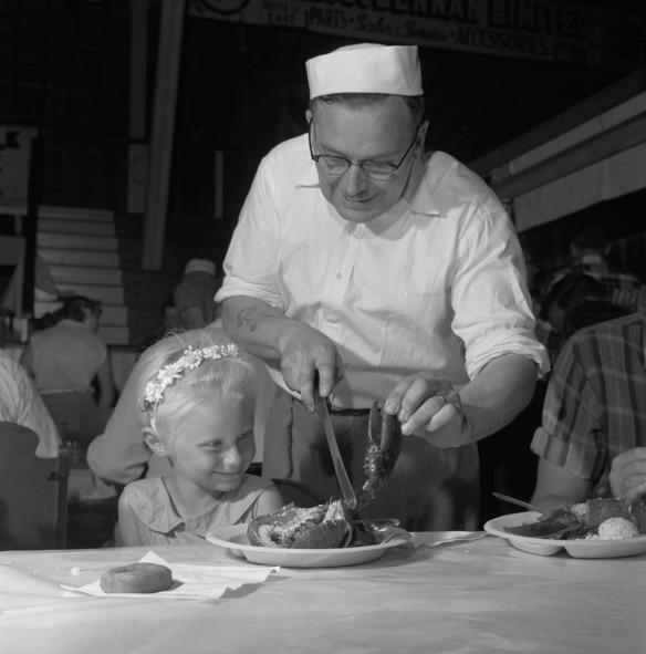 Photo noir et blanc d'un homme aidant une fillette attablée devant son repas de homard.