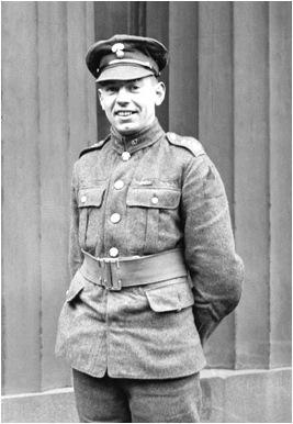Photo noir et blanc d'un soldat souriant, debout, les mains derrière le dos.