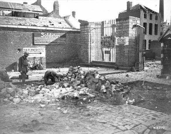 Photo noir et blanc d'un village où des bâtiments ont été endommagés. Au centre, on voit un imposant amas de pierres et de débris. Un soldat est agenouillé au sol, tout près. À gauche, un autre soldat se tient debout et l'observe.