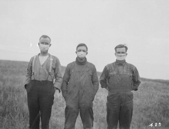 Photo noir et blanc montrant trois hommes portant des masques hygiéniques.