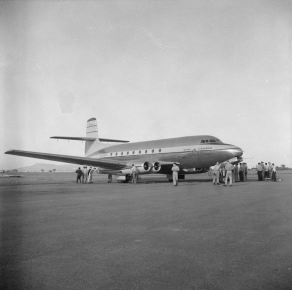 Photo noir et blanc d'un avion sur une piste, entouré de groupes d'hommes.