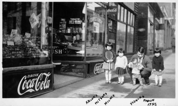 Photographie en noir et blanc montrant un Canadien japonais, en position accroupie, avec quatre enfants devant un commerce.