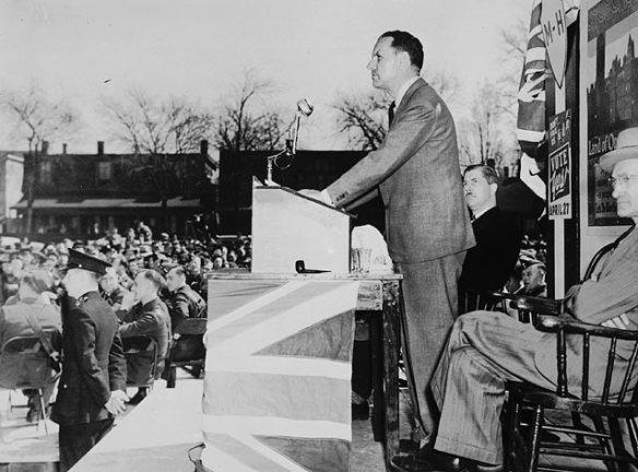Photo noir et blanc d'un homme debout derrière un lutrin, devant une foule de travailleurs. Le lutrin est recouvert d'un drapeau de l'Union royale. Des policiers font face à la foule.