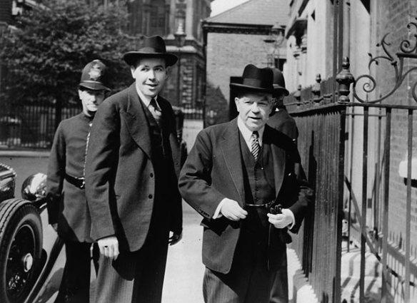 Photographie en noir et blanc montrant deux hommes debout près d'une haute clôture en fer. Un agent de police londonien est visible derrière eux.