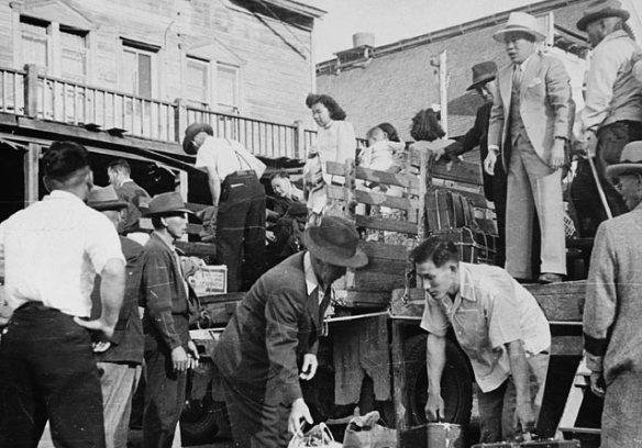 Photographie en noir et blanc montrant douze Canadiens japonais déchargeant un camion.