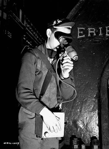 Photographie en noir et blanc d'un ouvrier qui regarde dans un pyromètre pour mesurer la température de l'acier en fusion.
