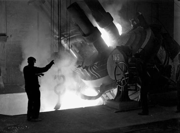 Photographie en noir et blanc d'un ouvrier, debout à côté d'un four, qui dirige le coulage d'acier en fusion dans une poche de coulée.