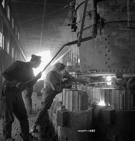 Photographie en noir et blanc d'ouvriers qui supervisent le coulage d'acier en fusion dans des moules.