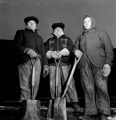 Photographie en noir et blanc de trois ouvrières du rail, portant des gants et de lourds vêtements de travail, et posant avec leurs pelles.