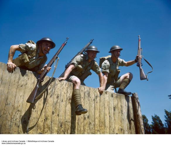 Photo couleur de trois hommes franchissant une palissade en bois, vêtus de casques, de chemises à manches courtes, de culottes courtes, de longues chaussettes et de bottes, et portant des fusils.