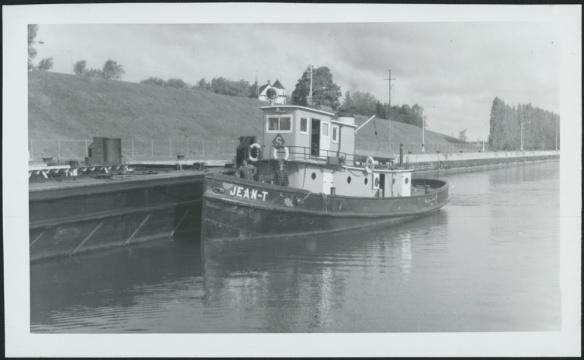 Photo noir et blanc d'un remorqueur à quai. L'équipage est sur le pont.