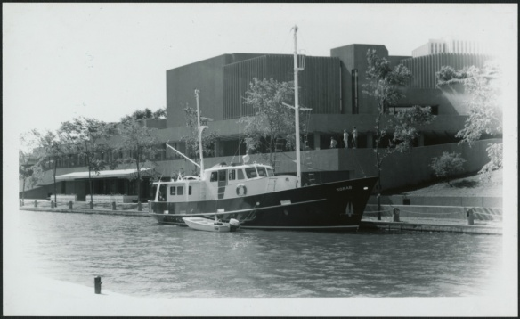 Photo noir et blanc d'un bateau de plaisance amarré le long d'un canal à proximité d'un imposant édifice.