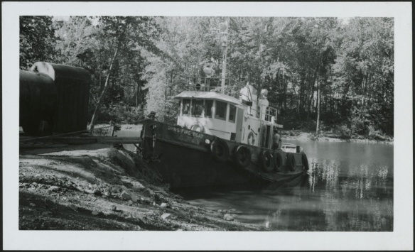 Photo noir et blanc d'un petit bateau-pompe amarré sur la rive boisée d'un cours d'eau.