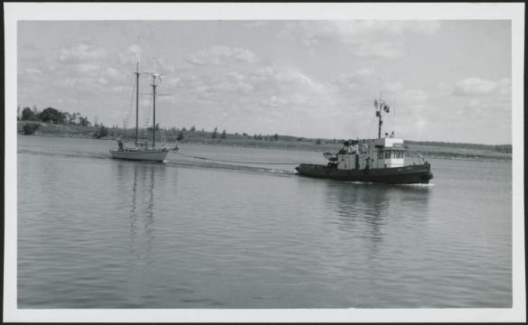 Photo noir et blanc d'un remorqueur tirant un voilier sur l'eau.