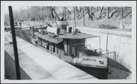 Photo noir et blanc d'un bateau de taille moyenne franchissant une écluse.