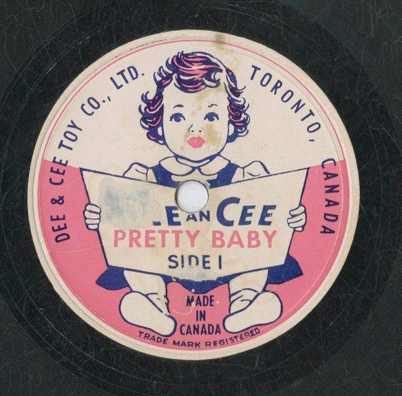 Une image en couleur d'une étiquette de disque de la compagnie de jouets Dee & Cee. La face 1 montre une petite fille assise tenant un livre ouvert. Le nom de la compagnie et le titre de l'enregistrement « Pretty Baby » apparaissent sur la couverture du livre.