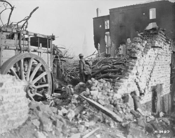 Photo noir et blanc d'un soldat en uniforme, dos à l'appareil photo, se tenant au milieu des décombres devant un bâtiment détruit. On aperçoit à gauche une charrette avec une grosse roue.