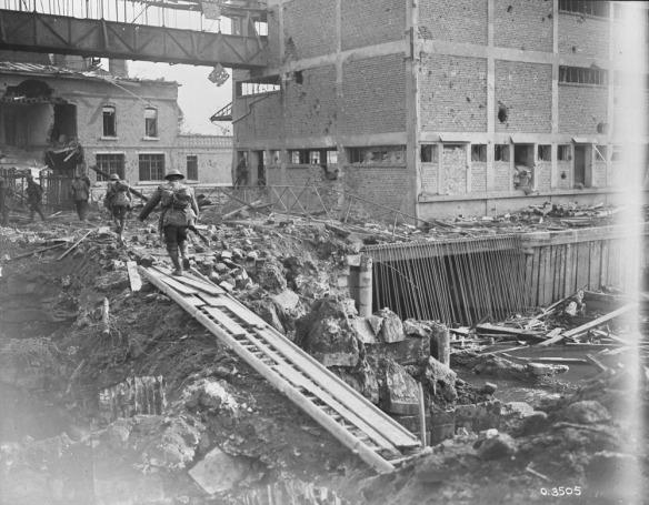 Photo noir et blanc de bâtiments en ruines dont les murs sont criblés de trous. Le sol est couvert de débris, de boue et de roches. Quatre soldats, de dos, s'éloignent de l'objectif après avoir traversé un pont improvisé fait de débris.