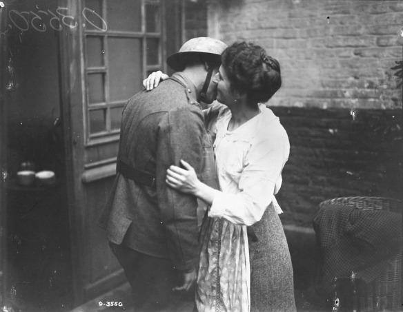 Photo noir et blanc d'une femme vêtue d'un chemisier blanc, embrassant sur la joue un soldat en uniforme qu'elle tient dans ses bras.
