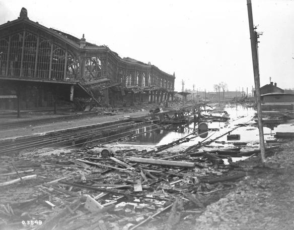 Photo noir et blanc d'une gare à l'architecture ouvragée, mais maintenant affaissée, avec des fenêtres brisées et des murs manquants. Le sol, séparé diagonalement par des rails, inondé et encombré de planches et de débris.