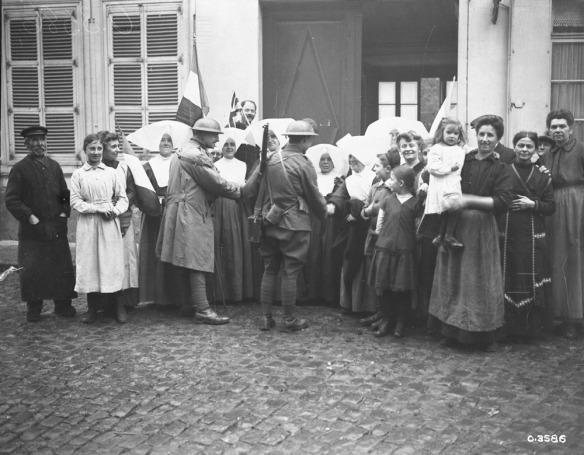 Photo noir et blanc d'un groupe de personnes se tenant devant un bâtiment dont la porte est ouverte. Des femmes portant de grandes coiffes blanches serrent la main de soldats en uniforme. De chaque côté, des groupes d'hommes et de femmes en habits civils sourient en regardant l'objectif. À l'arrière, quelqu'un tient un drapeau de la France.