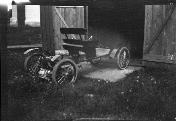 Photo noir et blanc d'une ancienne automobile garée à l'extérieur d'une grange.
