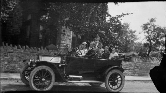 Photo noir et blanc d'un homme, d'une femme et de six enfants dans une voiture décapotable garée devant une maison.