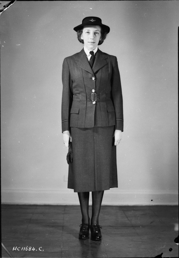 Photo noir et blanc d'une femme se tenant droite, vêtue d' un uniforme militaire composé d'une veste Norfolk, d'une jupe et de chaussures noires.