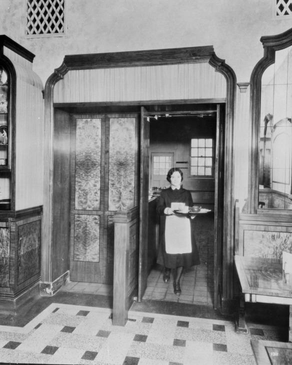 Photographie noir et blanc d'une femme sortant de la cuisine d'un restaurant en portant un plateau avec une théière et des tasses.
