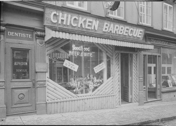 Photographie noir et blanc de l'extérieur du restaurant Nick's Chicken Barbecue. Une enseigne au néon dans la fenêtre annonce « Good Food » [bonne nourriture] et « Beer & Wine » [bière et vin].