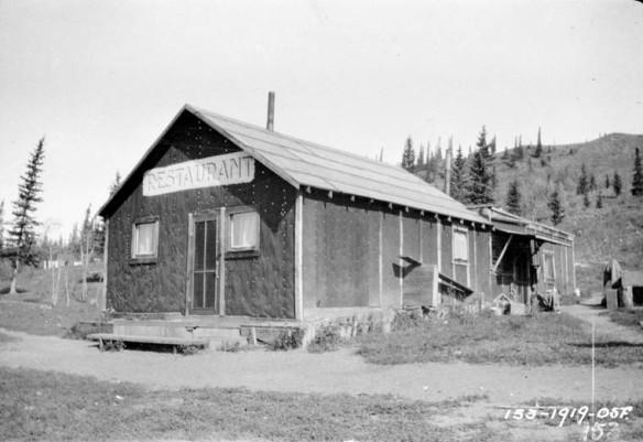 Photographie noir et blanc de l'extérieur d'un restaurant situé sur un chemin de terre dans une région éloignée.