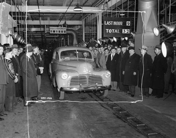 Photo noir et blanc d'une automobile sortant d'une ligne de production d'usine; des groupes d'hommes se tiennent debout de chaque côté du véhicule.